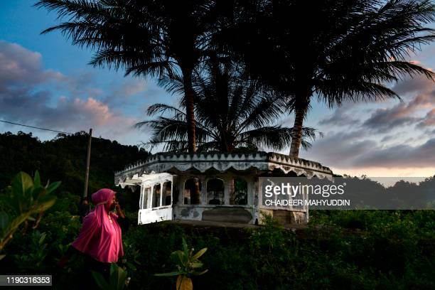 TOPSHOT A women walks past a mosque minaret devastated on 2004 by an earthquake and tsunami called 'Boxing Day Tsunami' in Lhokseudu Aceh province on...