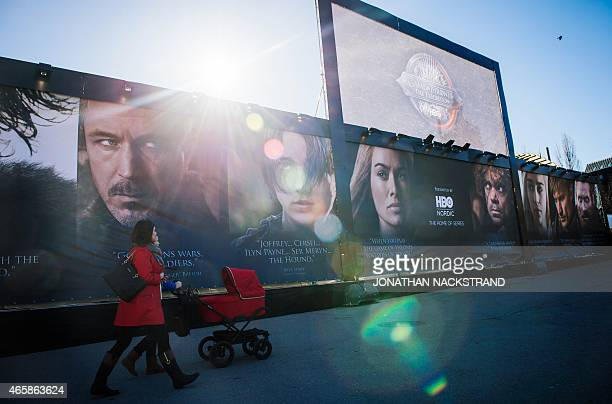 Women walks past an advertising poster to promote the HBO American fantasy drama television series Game of Thrones outside the International Game of...