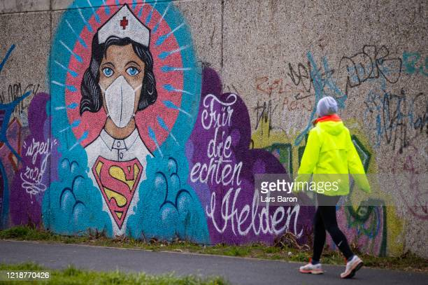 Women walks past street art painted by artist Kai 'Uzey' Wohlgemuth featuring a nurse as Superwoman on April 14, 2020 in Hamm, Germany. So far, over...