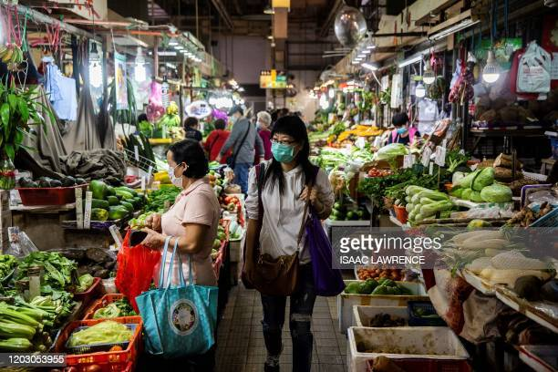 Women walks through the wet markets wearing a protective face mask in Hong Kong on February 25, 2020. - The new coronavirus has peaked in China but...