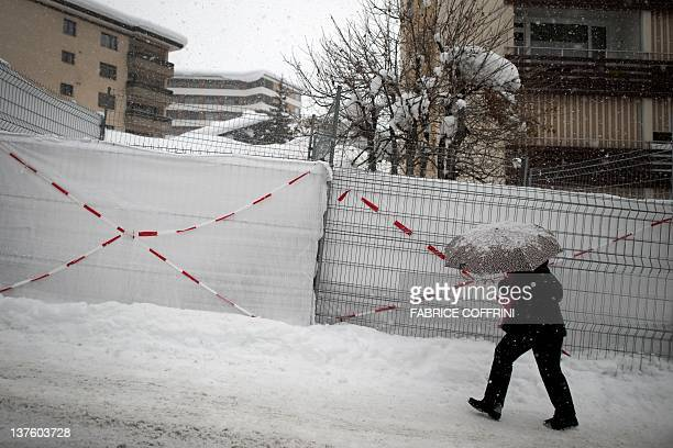 A women walks under snow next to fences at the resort of Davos on January 23 2012 Some 1600 economic and political leaders including 40 heads of...