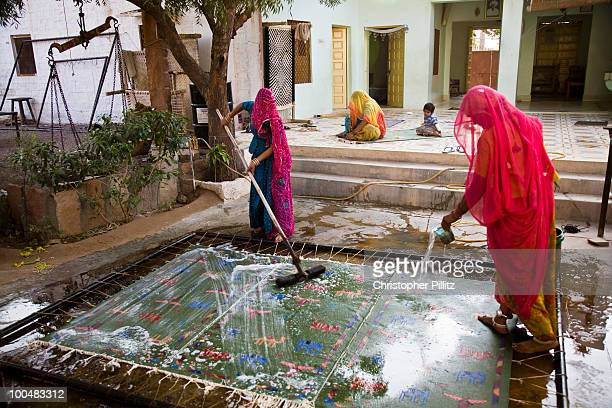 Women wash a newly weaved Dhurrie rug