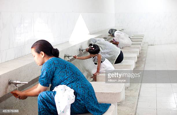 Women wash before praying at the National Mosque Baitul Mukarram during Eid alFitr on July 29 2014 in Dhaka Bangladesh Muslims around the world are...