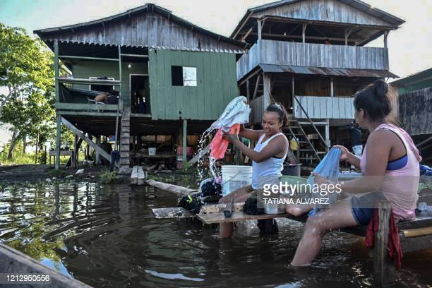 Women wash clothes at the Amazon river in Leticia, Colombia on May 13 amid the new coronavirus pandemic. - Colombia will increase the presence of...