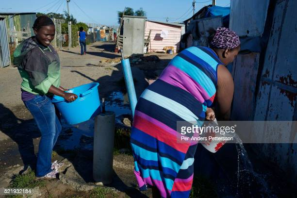 Women wash clothes with their children at a water tap in Guguletu a township about ten miles outside Cape Town South Africa Guguletu is one of the...