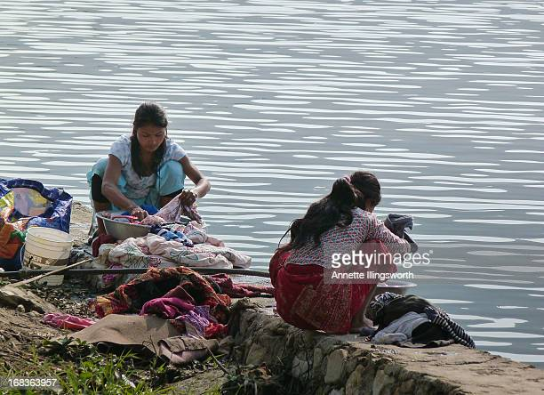 Women wash clothing & bedding by hand in the lake. Phewa Lake, Pokhara, Nepal. 2013