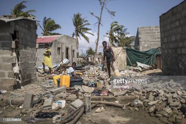 Women wash dishes amongst the rubble and debris from damaged houses in a residential neighborhood following the cyclone in Beira, Mozambique, on...