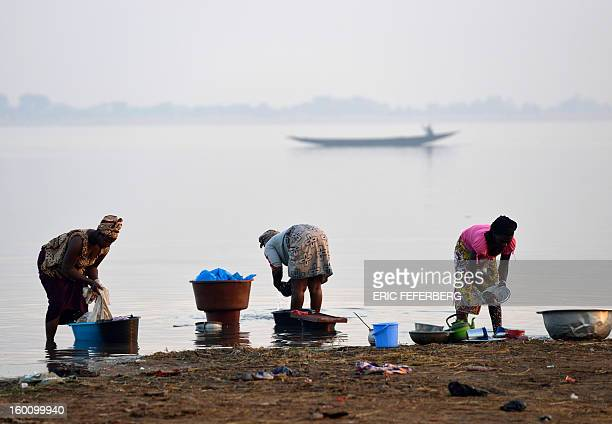 Women wash dishes in the Niger river on January 23 2013 in Segou 270km north of the capital Bamako AFP PHOTO / ERIC FEFERBERG