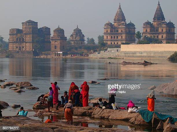 Women washing chlothes at the river. In the background are historical sites of orchha.