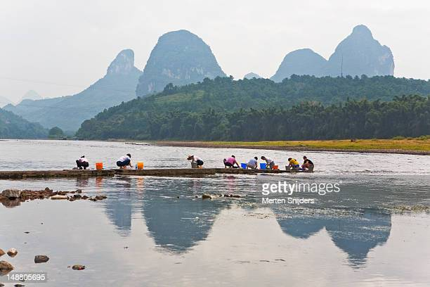 women washing clothes by li river with karsts in background. - merten snijders stock pictures, royalty-free photos & images