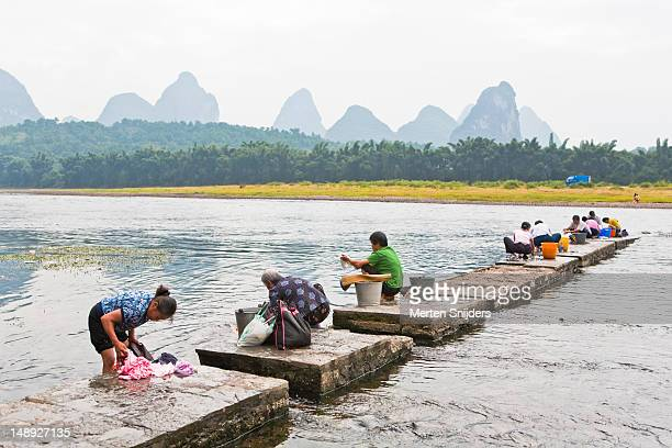 women washing clothes by li river with karsts in background. - merten snijders stockfoto's en -beelden