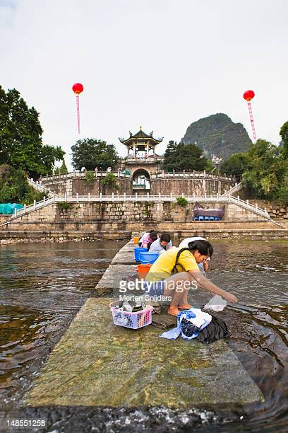 women washing clothes in li river. - merten snijders stock pictures, royalty-free photos & images