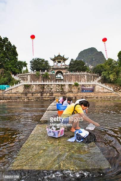 women washing clothes in li river. - merten snijders stock-fotos und bilder