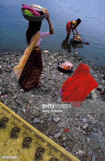 Women washing colourful clothes veils and saris on July 27 1985 in the Pichola Lake in Udaipur at Udaipur Rajasthan India The ghat where clothes are...