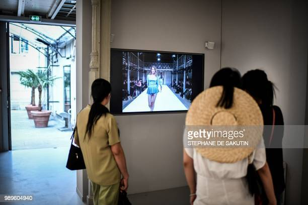 Women watch a film at the exhibition L'Alchimie Secrete d'Une Collection of late FrenchTunisian fashion designer Azzedine Alaia on July 2 2018 at the...