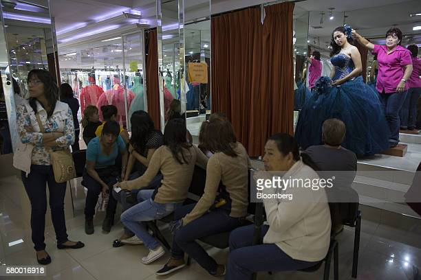 Women watch as a girl tries on a dress inside a dress store in Mexico city Mexico on Saturday July 23 2016 Mexican retail sales rose 86 percent in...