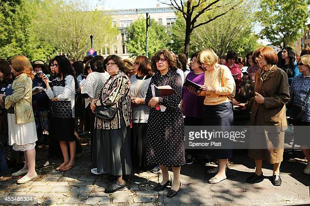 Women watch as mourners pay their respects to the coffin in a hearse outside the ChabadLubavitch headquarters during the funeral of Rabbi Joseph...