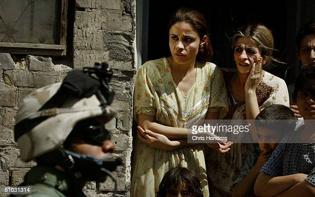 Women watch as US forces lead suspected insurgents away July 7 2004 in Baghdad Iraq Gunbattles broke out between resistance fighters and patrolling...