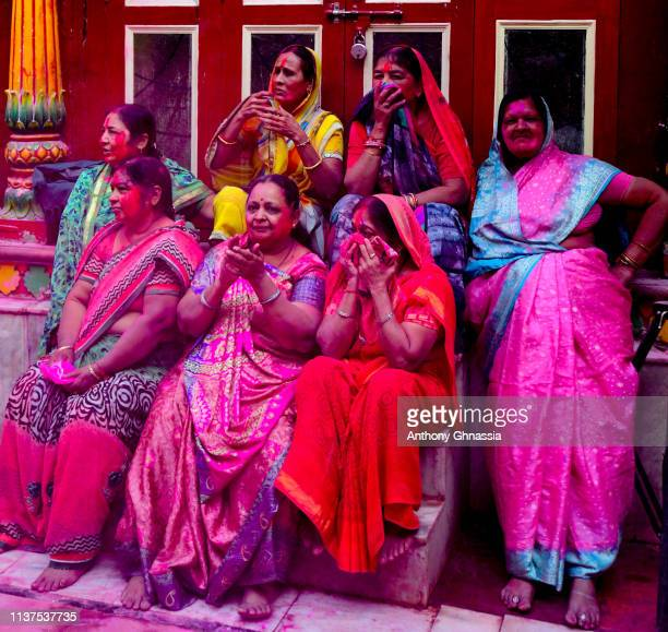 Women watch at the celebration of the Holi festival on March 21 2019 in Mathura India