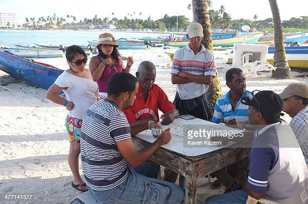Women watch fishermen play a game of dominoes while sitting at a table under palm trees on the beach near their boats on January 24 2014 in San...