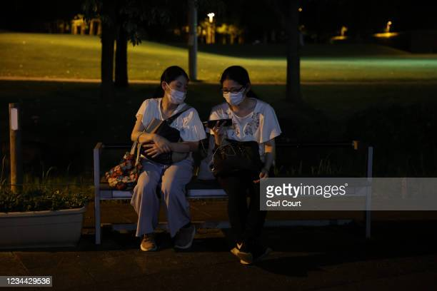 Women watch Japans mens semi-final match against Spain on a smartphone outside Saitama Stadium where the game is being played without spectators, on...