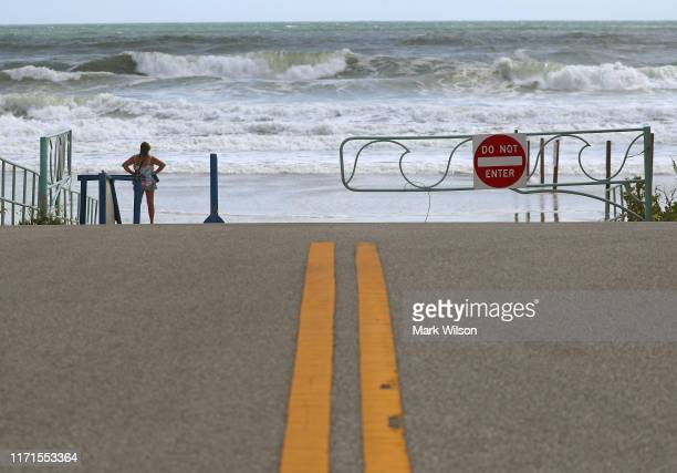 Women watches the Atlantic Ocean churn as Hurricane Dorian approaches on September 1, 2019 in Ponce Inlet, Florida. Dorian strengthened to a...