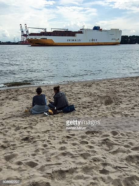 2 women watching a container ship in Hamburg Germany