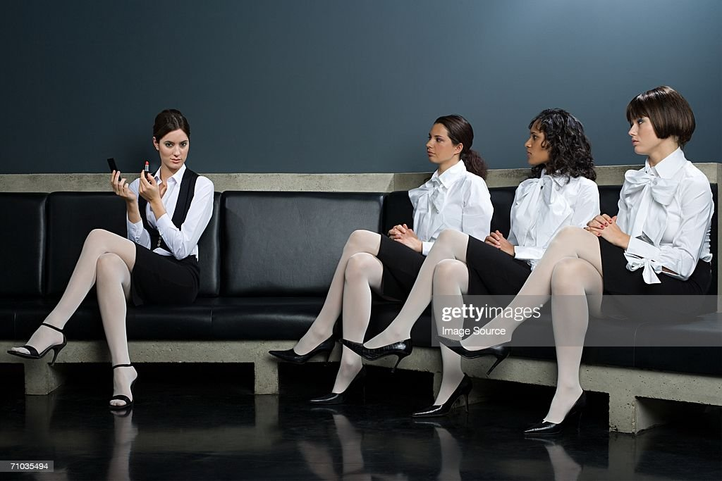 Women watching colleague apply lipstick : Stock Photo
