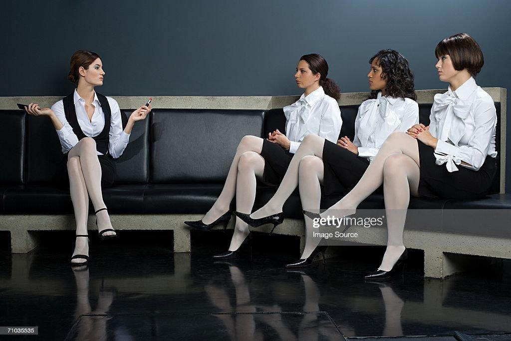 Women watching colleague apply lipstick : Stock Photo