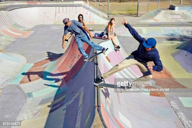 women watching men on skateboards at skate park - truco fotografías e imágenes de stock