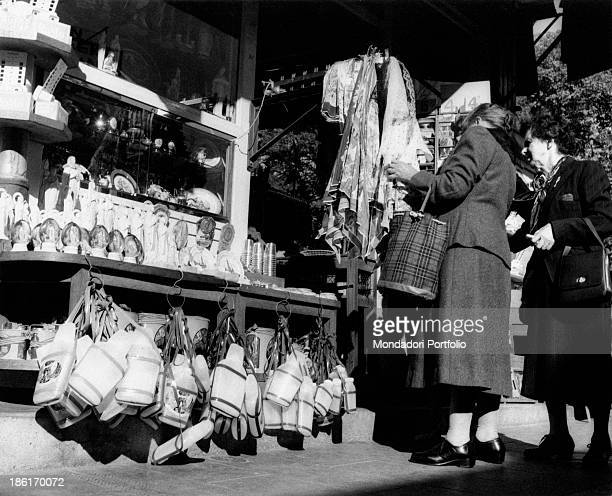 Women watching some items in a gift shop during the centenary of the apparitions of Our Lady to Saint Bernadette Soubirous Lourdes 22nd November 1957