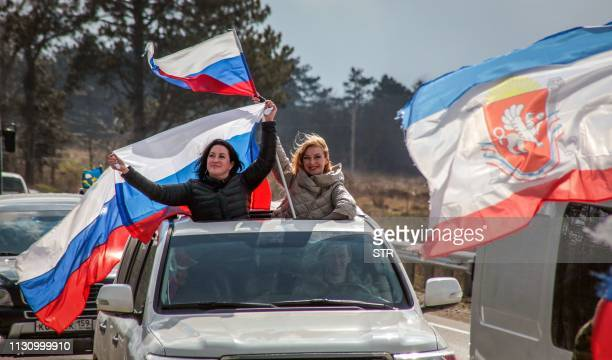 Women wave Russian flags to mark the fifth anniversary of Russia's annexation of Crimea, in Sevastopol on March 16, 2019.