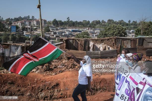 Women waves the Kenya national flag as women human rights defenders from 26 community based organisations march to commemorate International Women's...