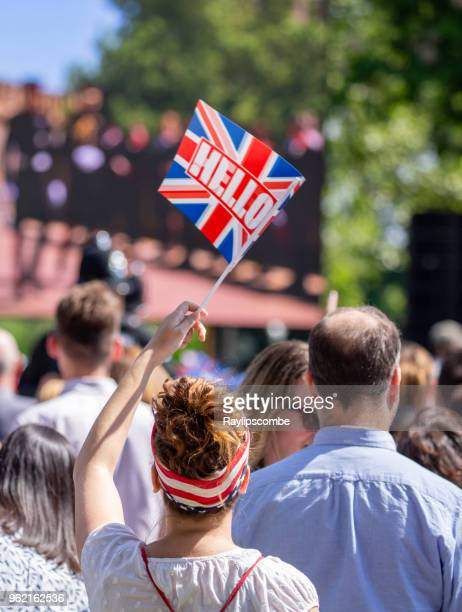 Women waving a union Jack flag amongst the crowds of people gathering in Windsor Great Park to celebrate the marriage of Meghan Markle and Prince Harry
