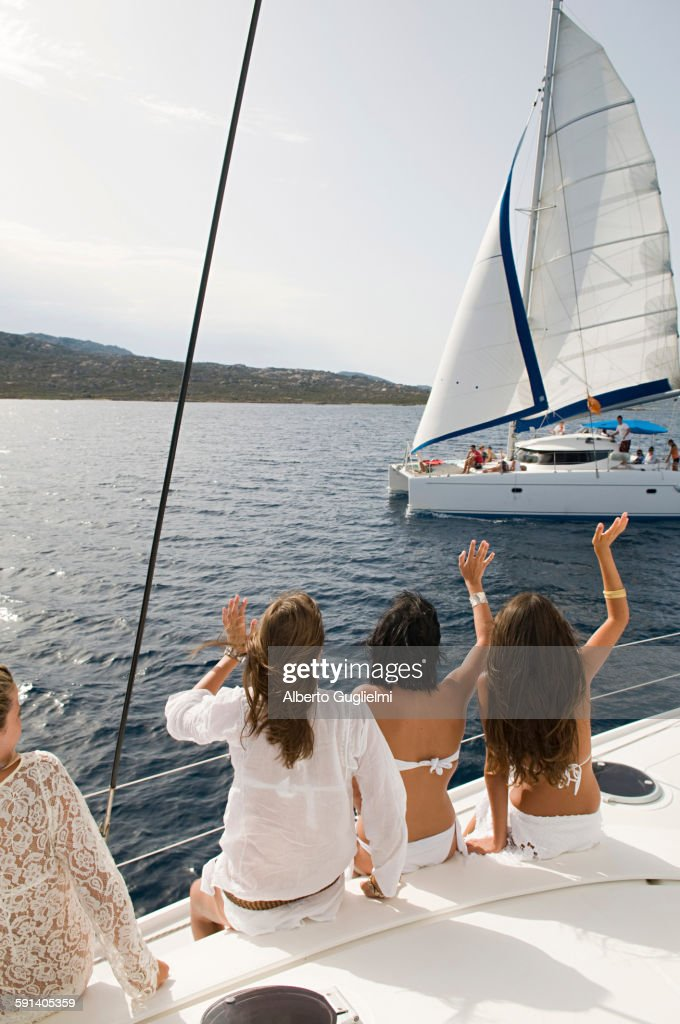Women waving from sailboat on ocean : Stock Photo