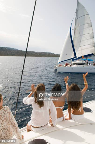 women waving from sailboat on ocean - catamaran stock photos and pictures