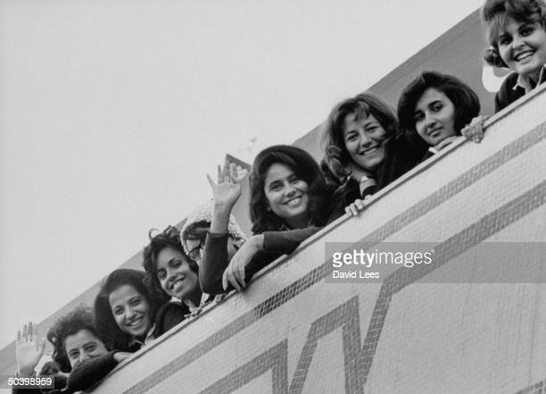 Women waving to Arab visiters arriving in Cairo for Summit Conference