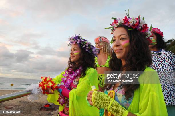 Women wear bright colours and flowers in their hair in solidarity with OneWave at sunrise on Bondi Beach on March 22 2019 in Sydney Australia Surfers...