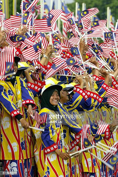 Women wear colourful costumes and wave Malaysian flags during the National Day celebrations in the eastern town of Kuantan 31 August 2004 Malaysia...