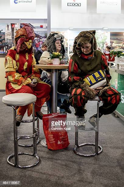 Women wear costumes as they sit at a table at the Gruene Woche agricultural trade fair on January 20 2014 in Berlin Germany The Gruene Woche is the...