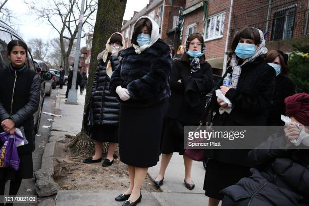 Women wear face masks as they join hundreds of members of the Orthodox Jewish community attending the funeral for a rabbi who died from the...