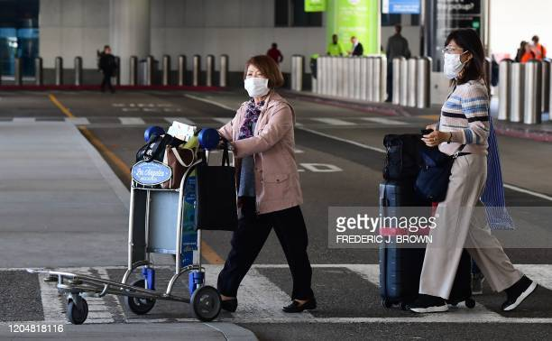 Women wear face masks at Los Angeles International Airport in Los Angeles California on March 2 2020 The number of US deaths from the novel...