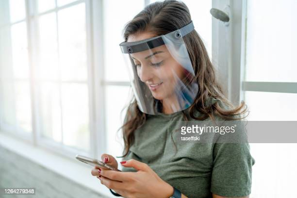 女性は自分を守るためにマスクと顔の盾を着用する - フェイスシールド ストックフォトと画像