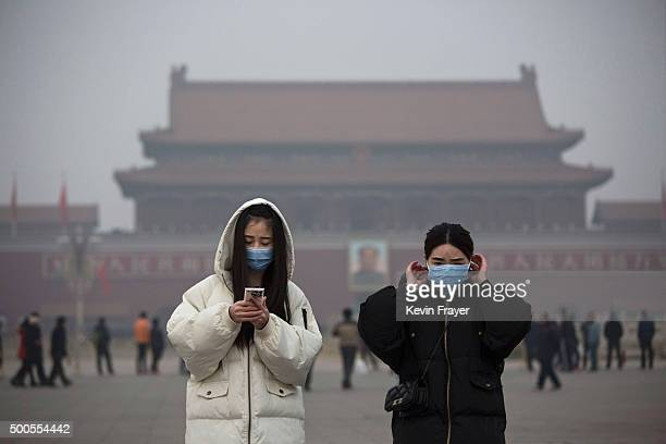 Women wear masks to protect against pollution as they visit Tiananmen Square during smog in Tiananmen Square on December 9 2015 in Beijing China The...