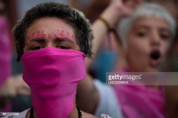 Women wear pink masks protesting the violence against women in Rio de Janeiro Brazil on November 28 2017 Around 100 people gathered in a march for...
