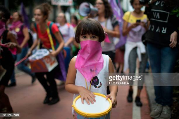 TOPSHOT Women wear pink masks protesting the violence against women in Rio de Janeiro Brazil on November 28 2017 Around 100 people gathered in a...