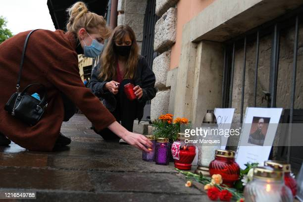 Women wear protective face masks as they light candles to place in a small memorial for George Floyd in front of the United States of America...