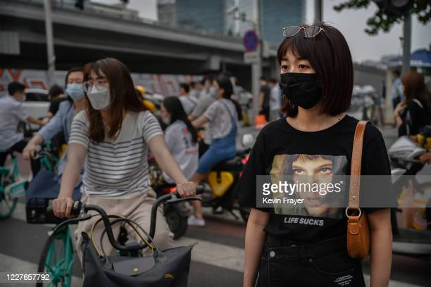 Women wear protective masks as they wait to cross an intersection during rush hour on July 17 2020 in Beijing China Chinas economy returned to growth...