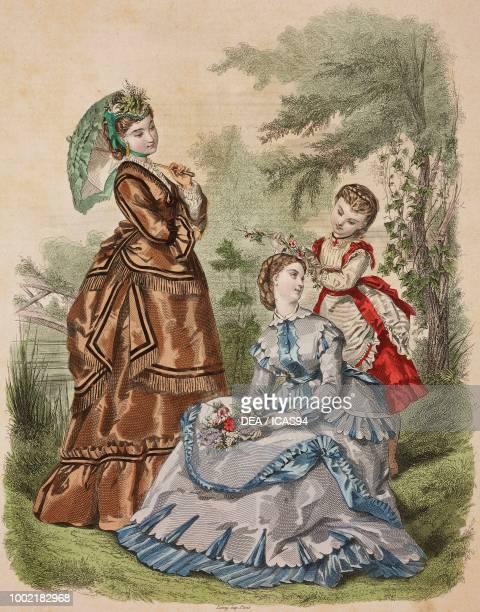 Women wearing a brown walking dress with black and fringed trim and light blue dress girl wearing white and red dress Madame Fladry designs France...