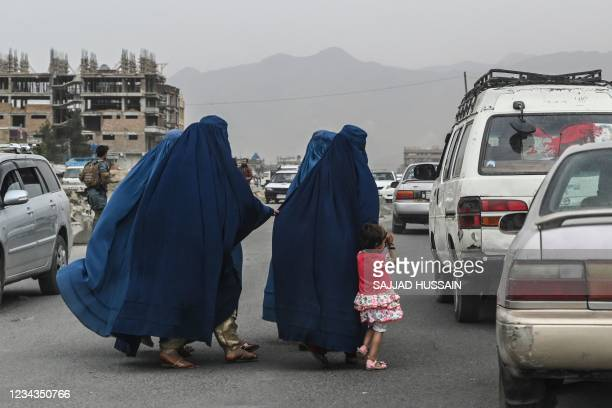 Women wearing a burqa cross a road as they walk towards a local taxi in Kabul on July 31, 2021.